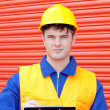 Confident worker writing on a clipboard — Stock Photo