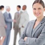 leende försäljare med armarna vikta och kollegor bakom henne — Stockfoto