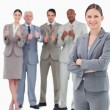 Smiling saleswoman with arms folded and her team behind her — Stock Photo