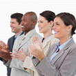 Stock Photo: Side view of clapping salesteam standing together