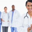 Smiling doctor with clipboard and members of staff behind her — Stock Photo #10322660