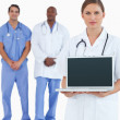 Female doctor showing laptop with colleagues behind her — Stockfoto