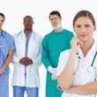Thoughtful doctor with male colleagues behind her - Stock Photo