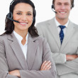 Stock Photo: Smiling call center agents with headsets and arms folded