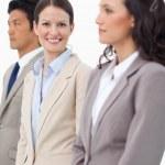Smiling saleswoman standing between colleagues — Stock Photo #10323057