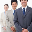 Smiling young salesteam standing in line — Stock Photo