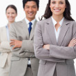 Smiling businesswoman with team and folded arms — Stock Photo