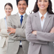 Smiling businessteam standing with folded arms — Stock Photo