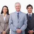 Stock Photo: Smiling mature businessman standing with team