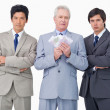 Senior businessman with money standing between his employees — Stock Photo