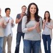 Clapping young woman with friends behind her - Stock Photo