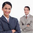 Smiling saleswoman with arms folded and colleague behind her — Stock Photo