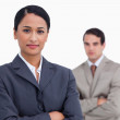 Saleswoman with arms crossed and colleague behind her — Stock Photo