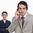 Hotline employee with colleague behind him — Stock Photo