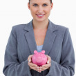 Smiling bank clerk holding piggy bank — Stock Photo