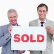 Smiling real estate agents holding sold sign — Stock Photo