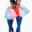Smiling teenagers looking behind them after shopping — Stock Photo