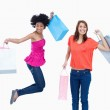 A teenage girl jumping with her shopping bags while her friend i — Stock Photo