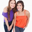 Two teenage girls leaning forward - Stock Photo