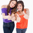 Teenagers putting their thumbs up while smiling - Stock Photo