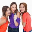 Three attractive young women singing in a microphone — Stock Photo