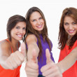 Happy teenagers standing side by side with their thumbs up - Stock Photo