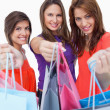 Smiling young women showing their purchases in front of the came - Stock Photo