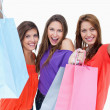 Three teenagers raising their arms while holding their purchases - Stock Photo