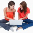 Smiling teenagers sitting cross-legged with a laptop - Stockfoto