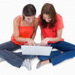 Two cute teenagers sitting cross-legged while looking at a lapto — Stock Photo