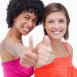 Smiling teenage girls proudly showing their thumbs up against a — Stock Photo