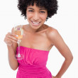Young woman holding a glass of champagne with her hand on her hi - Stock Photo