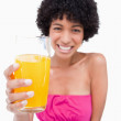 Glass of orange juice being held by a young smiling woman — Stock Photo