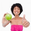 Smiling teenager holding a green apple and putting her thumbs up — Stock Photo #10327157