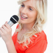Smiling woman singing with a microphone — Stock Photo
