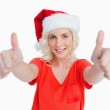 Smiling young woman putting her thumbs up in satisfaction — Stock Photo #10327551