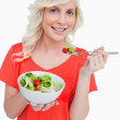 Young smiling woman eating a fresh salad with a fork — Stock Photo #10327556