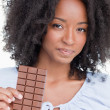 Stock Photo: Young woman holding a delicious chocolate bar