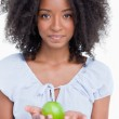 Young curly woman holding a green apple in her hands — Stock Photo #10327708