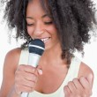 Young woman singing karaoke with a microphone — Stock Photo
