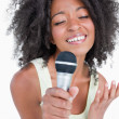 Concentrated young woman singing into a microphone — Stock Photo
