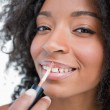 Young smiling woman making-up while using a lip gloss applicator — Stock Photo #10327833