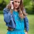 Stock Photo: Teenage girl using her mobile phone while looking at the camera