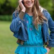 Smiling teenage girl talking on the phone while standing in a pa — ストック写真