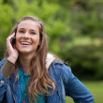 nastolatka za pomocą jej telefon komórkowy pokazując wielki uśmiech — Zdjęcie stockowe