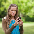 Stock Photo: Teenage girl sending a text while looking at the camera