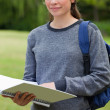 Young relaxed girl holding her notebook while carrying her backp — Stock Photo #10328207