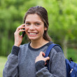 Young smiling girl talking on the phone while standing upright i — Stock Photo