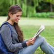 Young relaxed woman sitting on the grass while reading a book — Stock Photo #10328304