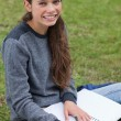 Smiling young woman writing on her notebook while looking at the — Stock Photo